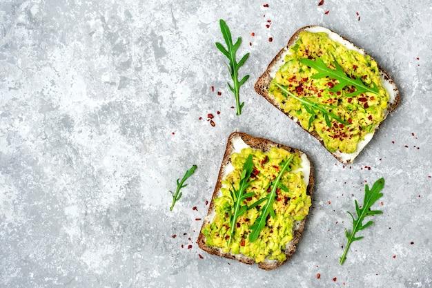 Zestaw kanapek na śniadanie - kromka ciemnego pieczywa pełnoziarnistego, twarożek, guakomole, przybrane
