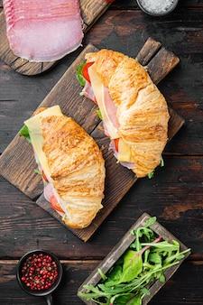 Zestaw kanapek rogalika, ziołami i składnikami, na tle starego ciemnego drewnianego stołu, leżał płaski widok z góry