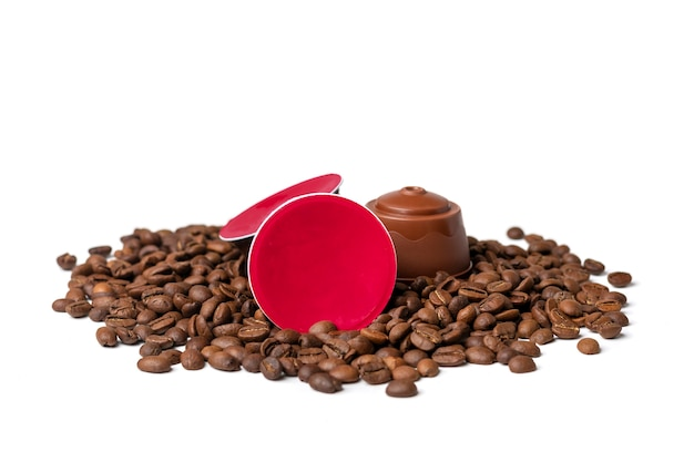 Zestaw kapsułek kawy, palonych ziaren na białym tle