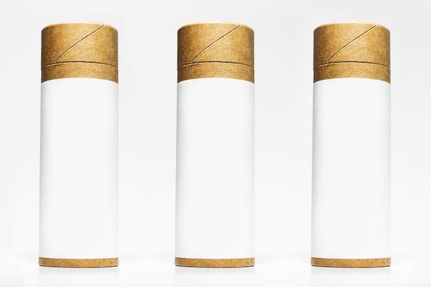 Zestaw kartonów cylindrycznych z pustą naklejką do makiety na białym tle na powierzchni białego studia