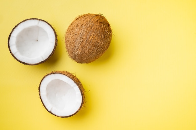 Zestaw kawałków coco, na żółtym tle z teksturą, widok z góry płaski, z miejscem na kopię tekstu