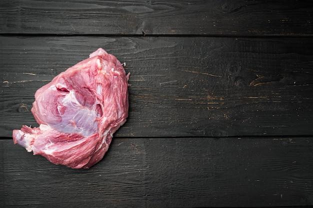 Zestaw kawałków surowego mięsa wieprzowego, na czarnym tle drewnianego stołu, widok z góry płaski, z miejscem na kopię tekstu