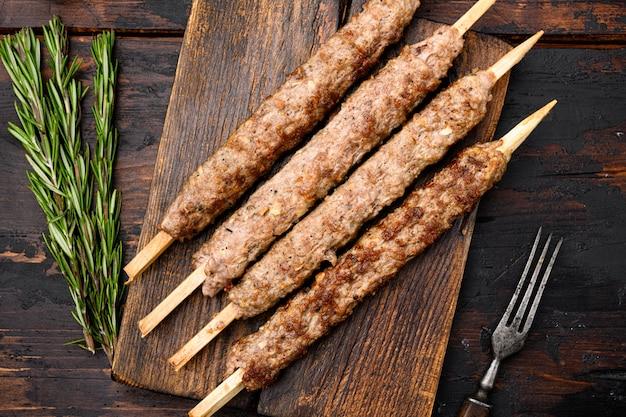Zestaw kebabów jagnięcych jagnięcych i baranich w kształcie, na desce do serwowania, na starym ciemnym tle drewnianego stołu, widok z góry płasko leżał
