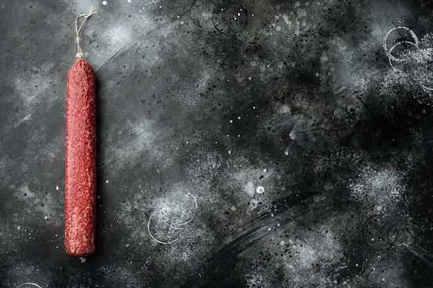Zestaw kiełbas salami, na czarnym ciemnym kamiennym stole, widok z góry na płasko