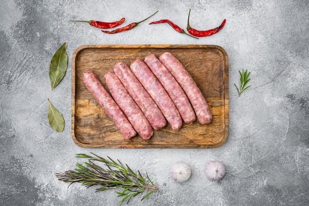 Zestaw kiełbasek z mięsa mielonego, na szarym tle kamiennego stołu, widok z góry płaski lay
