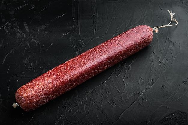 Zestaw kiełbasy salami wołowej, na czarnym ciemnym kamiennym stole