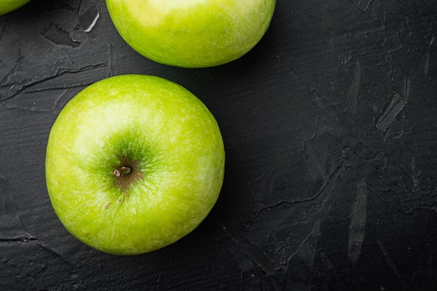 Zestaw kilku dojrzałych zielonych jabłek, na czarnym ciemnym tle kamiennego stołu, widok z góry płasko leżący, z miejscem na kopię na tekst