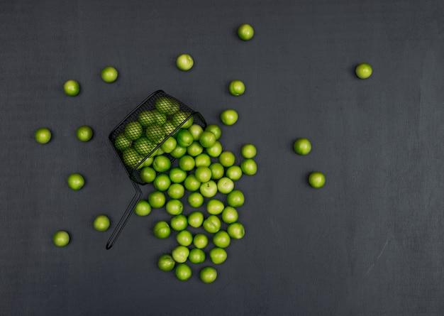 Zestaw kilku zielonych śliwek wiśniowych wokół niego i zielonej śliwki wiśniowej w czarnym koszu na czarnym tle. widok z góry. miejsce na tekst