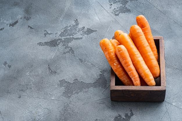 Zestaw kiści kolorowych pomarańczowych marchewek, w drewnianym pudełku, na szarym tle, z copyspace i miejscem na tekst