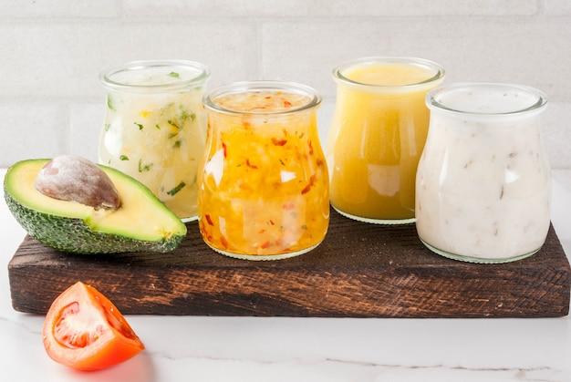 Zestaw klasycznych sosów sałatkowych - musztarda miodowa, ranczo, winegret, cytryna i oliwa z oliwek, na stole z białego marmuru, copyspace