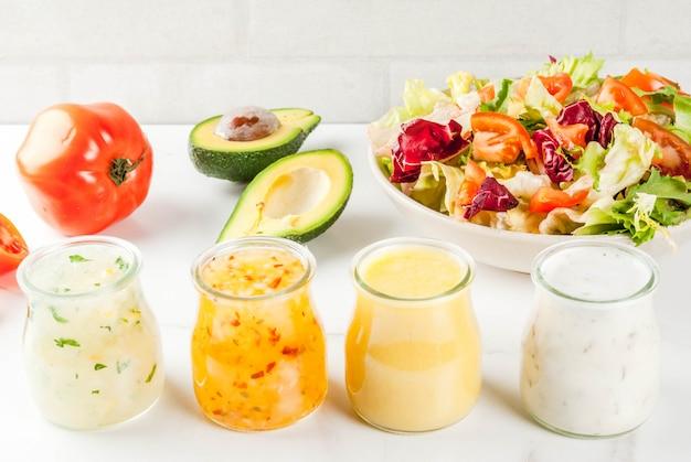 Zestaw klasycznych sosów sałatkowych z musztardą, rancho, winegretem, cytryną i oliwą z oliwek, na białym marmurowym stole,