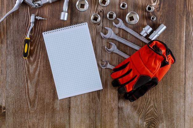 Zestaw kluczy do naprawy srebrnych kluczy leżących po bokach i spiralnego notatnika profesjonalnych rękawic roboczych do narzędzi samochodowych