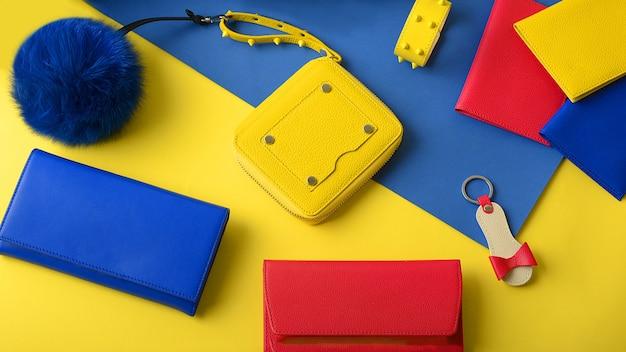 Zestaw kolorowych akcesoriów skórzanych: mała kobieca żółta torebka, portfele, brelok w formie buta, puszysty brelok. widok z góry. leżał na płasko. jasna wizytówka sklepu z akcesoriami skórzanymi.