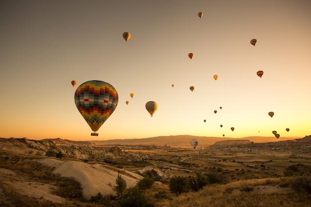 Zestaw kolorowych balonów latających nad ziemią w kapadocji, turcja