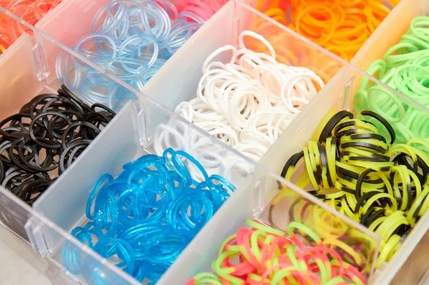 Zestaw kolorowych gumek i dzianiny do robienia na drutach opasek na rękę