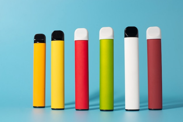 Zestaw kolorowych jednorazowych papierosów elektronicznych z cieniami. koncepcja nowoczesnego palenia, waporyzacji i nikotyny. widok z góry.