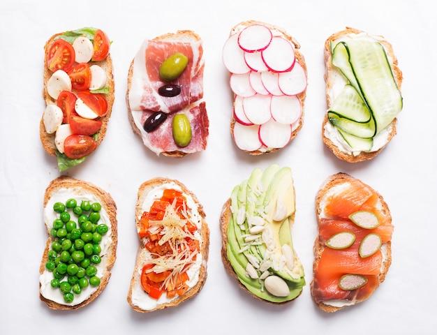 Zestaw kolorowych kanapek przygotowanych z różnych składników, takich jak ryby, warzywa i mięso. widok z góry