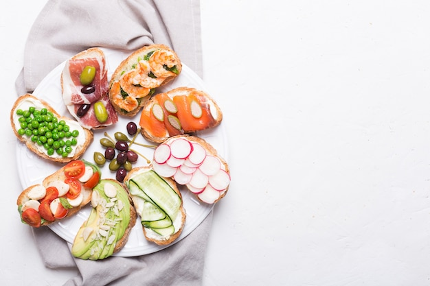 Zestaw kolorowych kanapek przygotowanych z różnych składników, takich jak ryby, warzywa i mięso