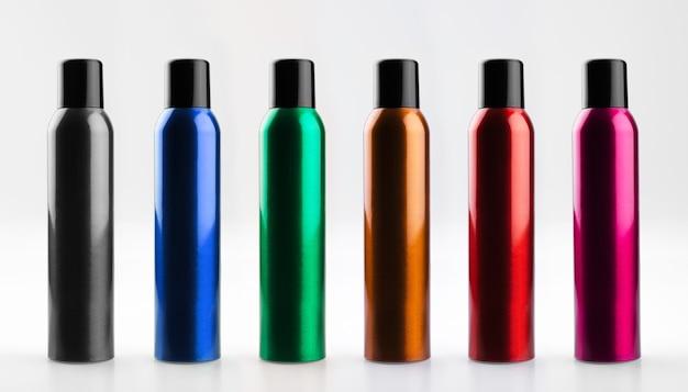 Zestaw kolorowych, kosmetycznych puszek aerozolu z aluminium z nakrętkami. butelki kosmetyczne z lakierem do włosów.