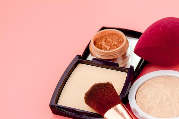 Zestaw kolorowych kosmetyków na różowym drewnianym stole, baza pod makijaż w postaci poduszki. skopiuj miejsce