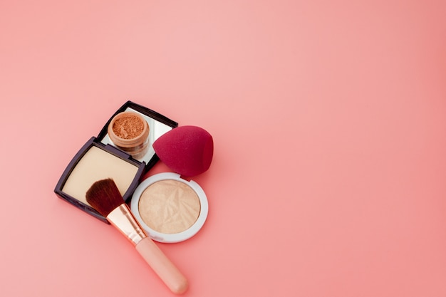 Zestaw kolorowych kosmetyków na różowym drewnianym stole w tle, baza pod makijaż w postaci poduszki. skopiuj miejsce