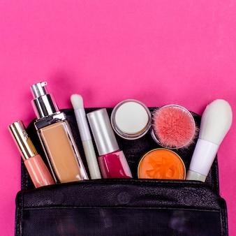 Zestaw kolorowych kosmetyków na różowym stole