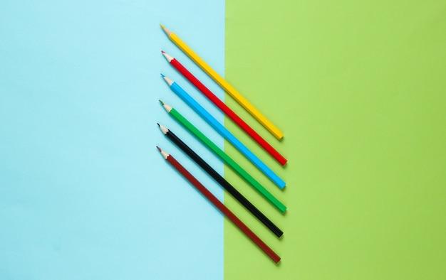 Zestaw kolorowych kredek na pastelowej powierzchni.