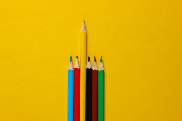 Zestaw kolorowych kredek na żółtej powierzchni. koncepcja wyjątkowości.
