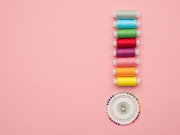 Zestaw kolorowych nici i szpilki ustawione do robótek ręcznych na różowym tle z miejsca kopiowania.