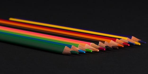 Zestaw kolorowych ołówków na czarnym tle na białym tle. powrót do szkoły