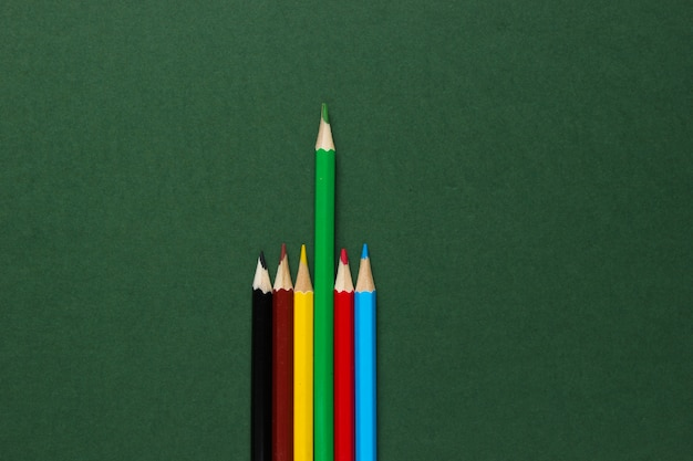 Zestaw kolorowych ołówków na zielonej powierzchni. koncepcja wyjątkowości.