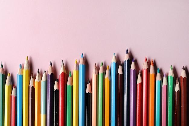 Zestaw kolorowych ołówków, wiersz drewniane kolorowe kredki na białym tle na różowym tle.
