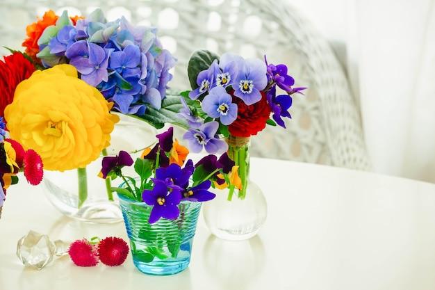 Zestaw kolorowych świeżo ściętych kwiatów w szklanych wazonach na białym pulpicie