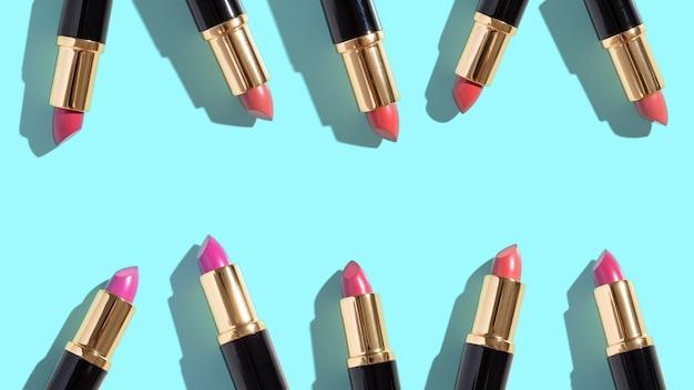 Zestaw kolorowych szminek na kolorowym tle. profesjonalne kosmetyki dekoracyjne, produkt promocyjny pomada do reklamy. widok z góry na płasko