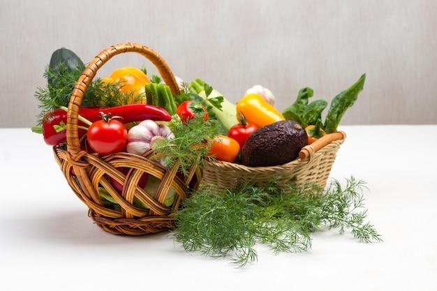 Zestaw kolorowych warzyw w dwóch wiklinowych koszach. koper na stole. skopiuj miejsce. białe tło.