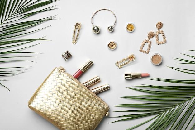 Zestaw kosmetyków dekoracyjnych, akcesoriów i tropikalnych liści na jasnym tle