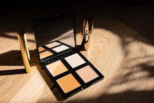Zestaw kosmetyków dekoracyjnych. cień do powiek i szminka w złotym opakowaniu na drewnianym tle
