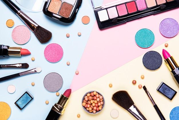 Zestaw kosmetyków dekoracyjnych na kolorowe tło, widok z góry