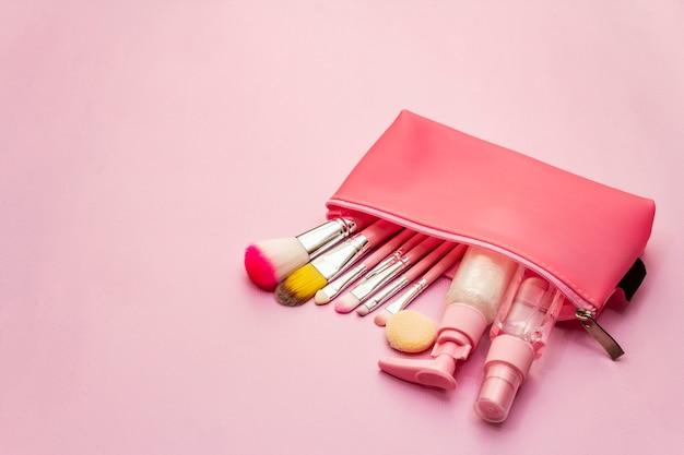 Zestaw kosmetyków do makijażu w torbie na różowym tle