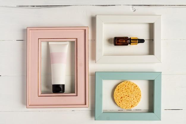 Zestaw kosmetyków do oczyszczania i leczenia skóry twarzy. pusta tubka kosmetyczna ze środkiem czyszczącym, buteleczką serum i gąbką w ramkach