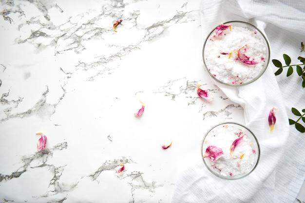 Zestaw kosmetyków do pielęgnacji skóry i ciała, sól morska na szarym marmurowym stole. pojęcie piękna procedur salonowych. leżał płasko, widok z góry