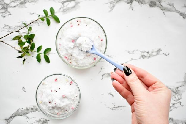 Zestaw kosmetyków do pielęgnacji skóry i ciała, sól morska na szarym marmurowym stole.