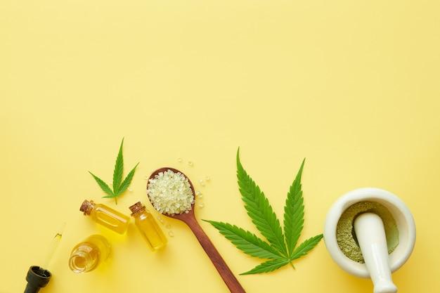 Zestaw kosmetyków do pielęgnacji skóry konopi w makietowym opakowaniu. krem nawilżający, serum, balsam, olejek cbd, olejek eteryczny z liści konopi. przestrzeń płaska świeckich kopii. na żółtym tle.