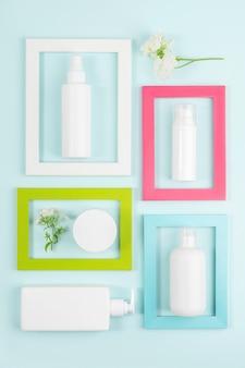 Zestaw kosmetyków do pielęgnacji skóry twarzy, ciała, dłoni. białe puste butelki kosmetyczne, rurki, słoiki, kwiaty w jasnych ramkach na niebieskim tle. koncepcja kreatywnych kosmetycznych urody. widok z góry makieta.