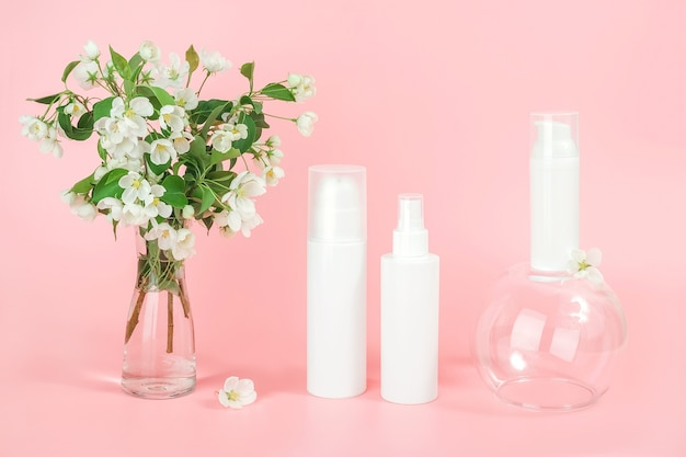 Zestaw kosmetyków do pielęgnacji twarzy, ciała. białe puste butelki kosmetyków i tuba na szklanym podium