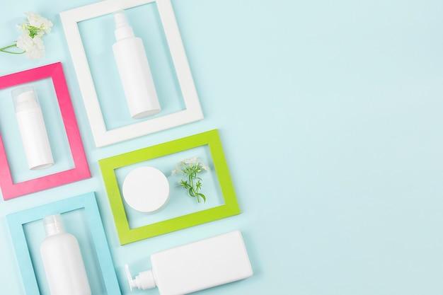 Zestaw kosmetyków do pielęgnacji twarzy, ciała, dłoni. biała pusta butelka kosmetyczna, tubka, słoik, kwiaty w jasnych ramkach na niebieskim tle.