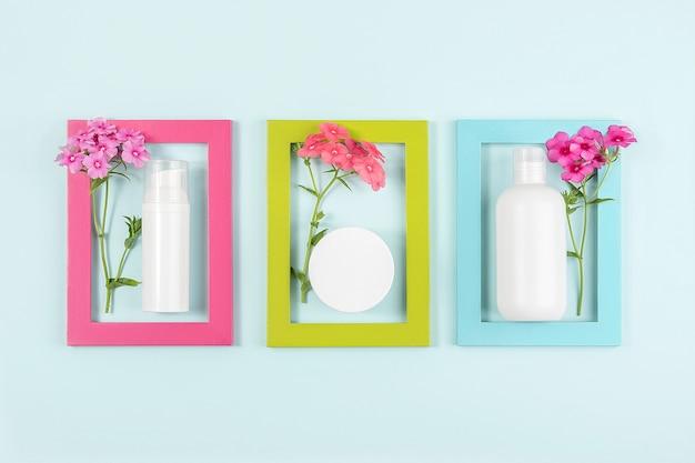 Zestaw kosmetyków do pielęgnacji twarzy, ciała, dłoni. biała pusta butelka kosmetyczna, tubka, słoik, kwiaty w jasnych ramkach na niebiesko