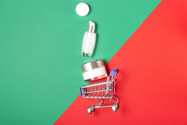 Zestaw kosmetyków do twarzy i ciała oraz wózek na zakupy na jasnoczerwonym i zielonym tle. koncepcja zakupu kosmetyków, sklepu internetowego, wakacji