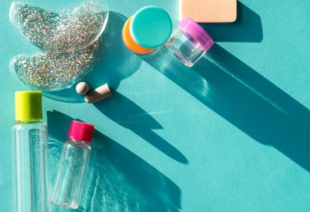 Zestaw kosmetyków kosmetycznych i kremów w rozmiarze podróży, podkładki pod oczy, zatyczki do uszu na miętowym niebieskim tle.