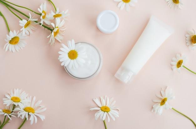 Zestaw kosmetyków naturalnych. pojemniki z kremem i kwiatami rumianku na stole